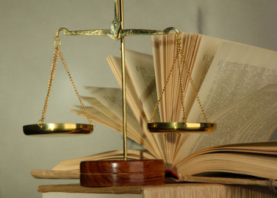 scales of justice with legal journals