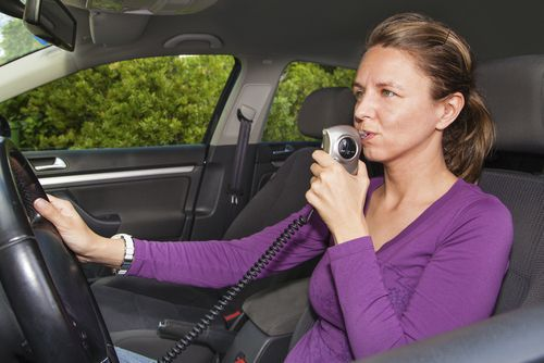 Woman breathing into ignition interlock device